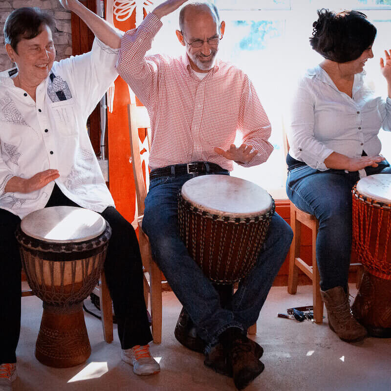 People playing djembe drums.
